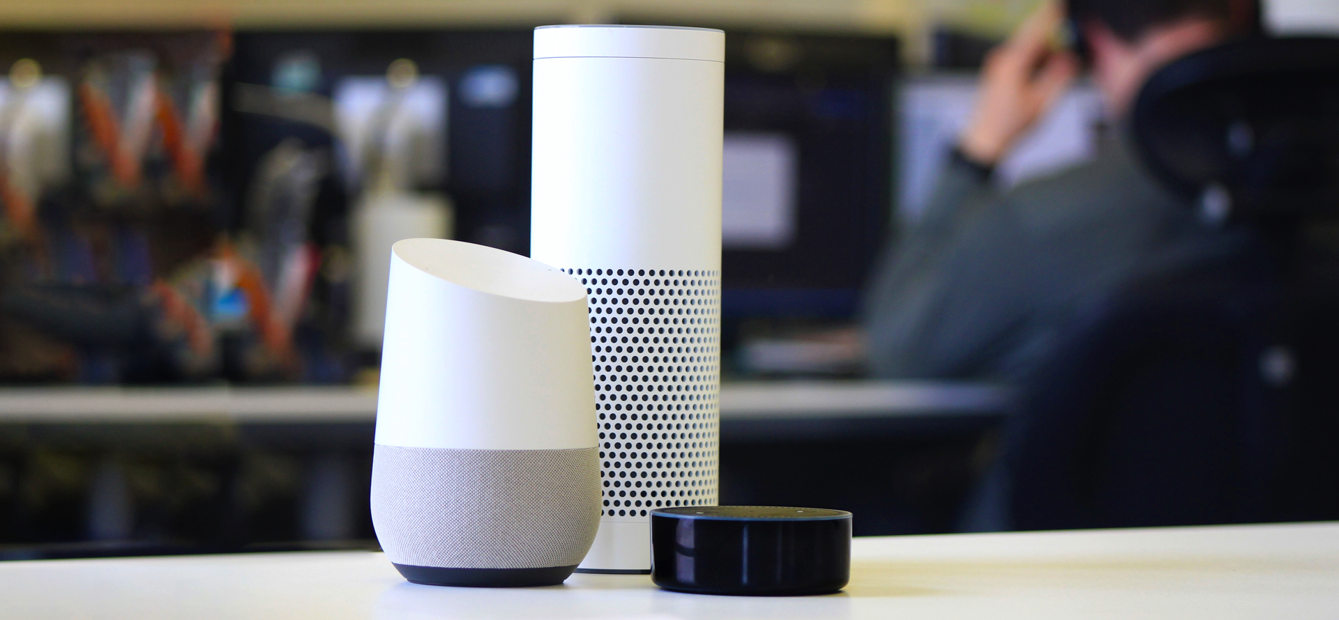 Image of google home, amazon echo, and amazon echo dot devices sitting on a desk