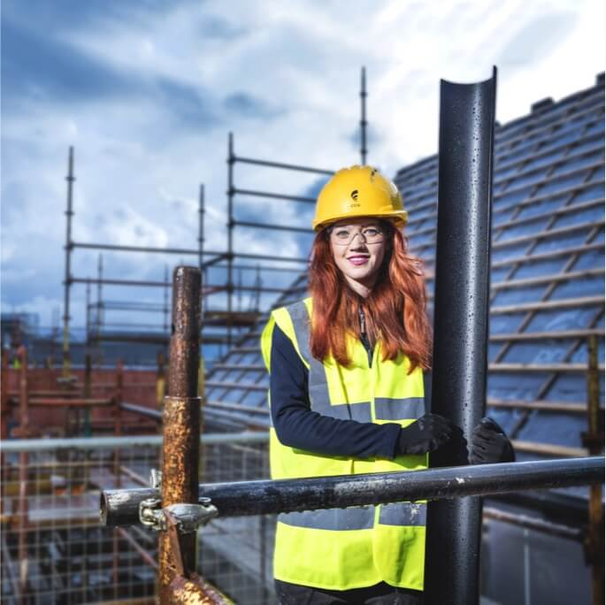 A young female modern apprentice in high vis clothing and a hard hat, standing on scaffolding on a roof