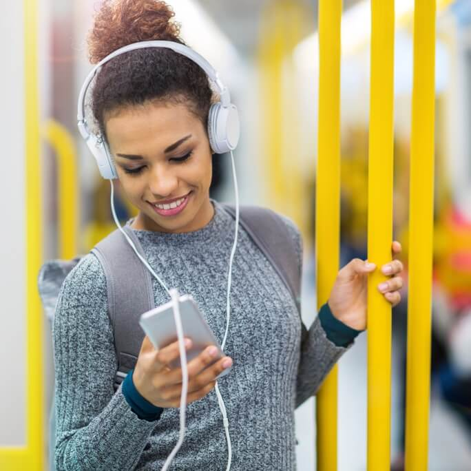 Female traveller on the subway, listening to music and smiling while looking at her phone