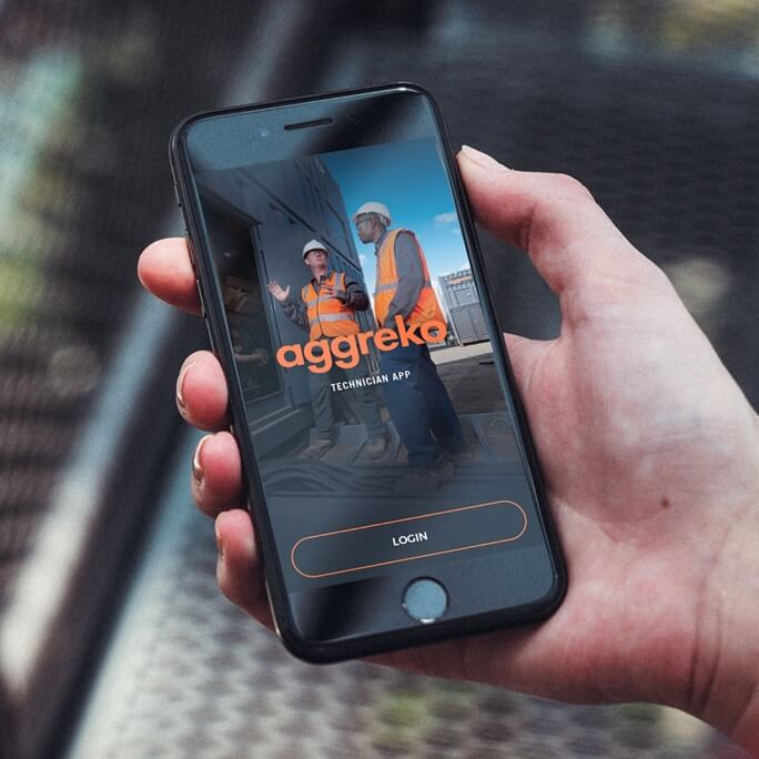 A hand holding a mobile device with the aggreko technician app open