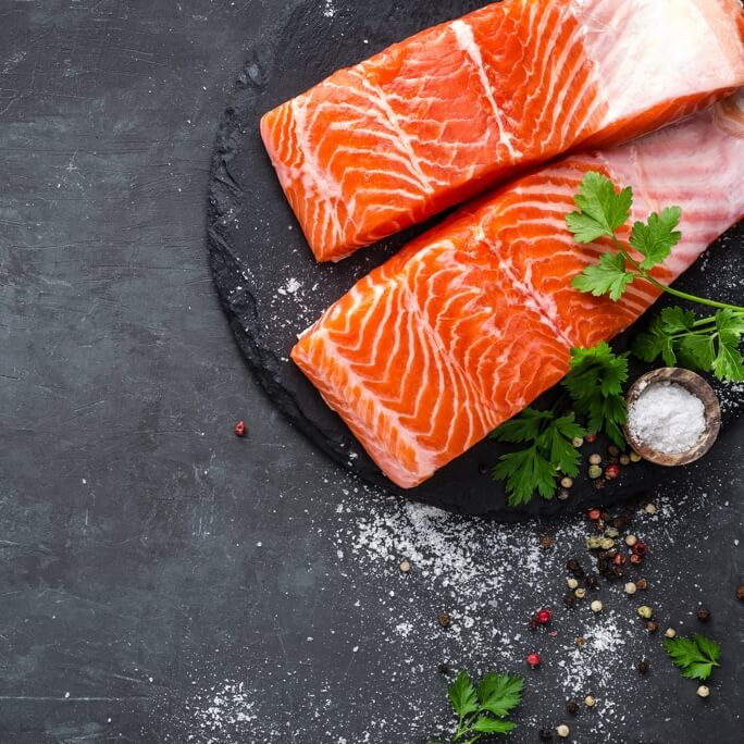 A Scottish dish of salmon on a stone plate with sea salt scattered around it and garnish