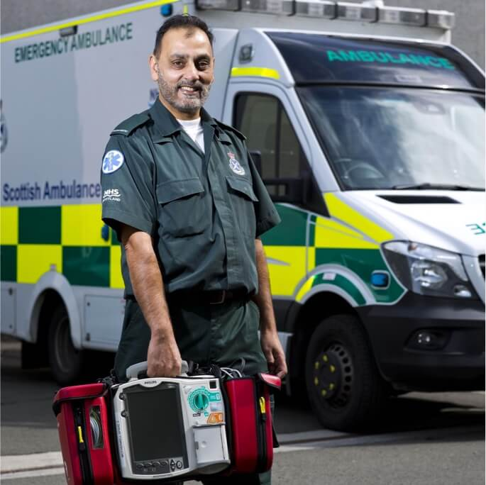 Paramedic with equipment in front of an ambulance